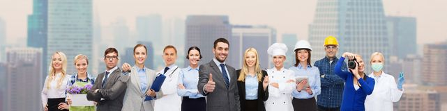 Happy businessman over professional workers. People, profession, qualification, employment and success concept - happy businessman over professional workers Royalty Free Stock Photo