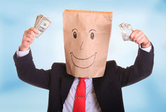 Happy businessman with a paper bag on head with money stock photo