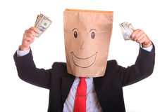 Happy businessman with a paper bag with smile on head holds money in his hand Royalty Free Stock Photography