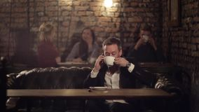 Happy businessman with phone in a cafe drinking coffee. Talking on the phone stock footage