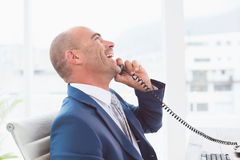 Happy businessman on the phone laughing Stock Photography