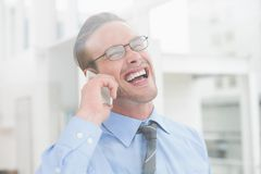 Happy businessman on the phone laughing Stock Photos