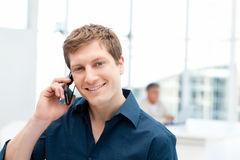 Happy businessman phoning in his office. At work Royalty Free Stock Photography