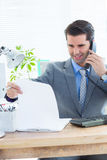 Happy businessman phoning and looking note Stock Images