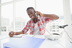 Happy businessman phoning and taking notes Stock Image