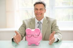 Happy businessman with piggybank on desk Royalty Free Stock Photography