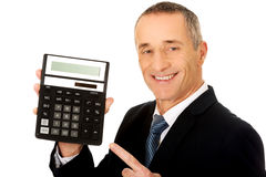 Happy businessman pointing on calculator Royalty Free Stock Image