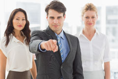 Happy businessman pointing to camera in front of his team Stock Photos