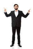 Happy businessman points his finger up. Stock Photos