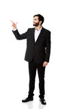 Happy businessman points his finger up. Royalty Free Stock Photo