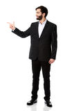 Happy businessman points to the left. Stock Images