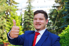 Happy businessman. Portrait of a handsome and successful man showing thumbs up Royalty Free Stock Photo