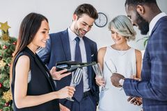 Happy businessman pouring champagne to multicultural colleagues glasses. In office royalty free stock photos