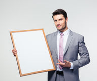 Happy businessman presenting blank board Stock Images