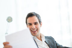 Happy Businessman Reading a Document at his Office Stock Photo