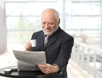 Happy businessman reading newspaper Royalty Free Stock Images