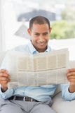 Happy businessman reading newspaper on the couch Royalty Free Stock Photos