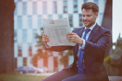 Happy businessman reading newspaper Stock Images