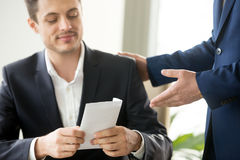 Happy businessman receiving white envelope with bribe, bribery c. Happy corrupted businessman accepting bribe, male hand giving smiling office worker envelope Stock Photography