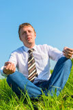 Happy businessman relaxes in a field Stock Image
