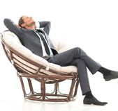 Happy businessman relaxing in big comfortable armchair. Photo has a blank space for text Royalty Free Stock Images