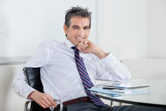 Happy Businessman Relaxing In Office Stock Photo