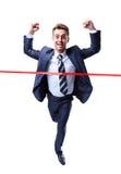 Happy businessman running through finishing line Royalty Free Stock Image