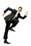 Happy businessman runs in black suit on white. Royalty Free Stock Photography