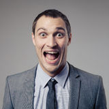 Happy Businessman Screaming on gray background. Happy Young Businessman Screaming on gray background Royalty Free Stock Photography
