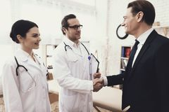 Happy businessman shaking hands with doctor who cured ailment. Acknowledgments. Medical examination. Treatment of disease stock photo