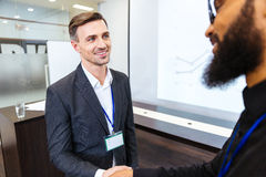 Happy businessman shaking hands with young colleague Royalty Free Stock Photo