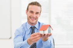 Happy businessman showing miniature house Royalty Free Stock Photography