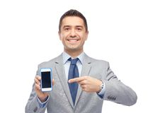 Happy businessman showing smartphone screen royalty free stock photo