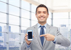 Happy businessman showing smartphone screen. Business, people and technology concept - happy smiling businessman in suit showing smartphone black blank screen Stock Photography