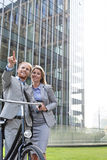 Happy businessman showing something to businesswoman in city Royalty Free Stock Photo