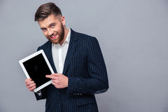 Happy businessman showing tablet computer screen. Portrait of a happy businessman showing tablet computer screen over gray background Stock Image