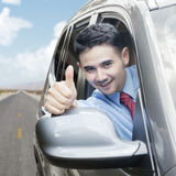 Happy businessman showing thumb up in car Royalty Free Stock Image