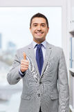 Happy businessman showing thumbs up in office Stock Images