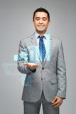 Happy businessman showing virtual chart projection Stock Photo
