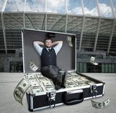 Happy businessman sits in the case full of dollars. Outdoors royalty free stock images
