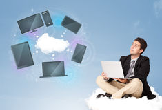 Happy businessman sitting on cloud enjoying cloud network servic Royalty Free Stock Photos