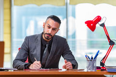 The happy businessman sitting at the desk Stock Photo
