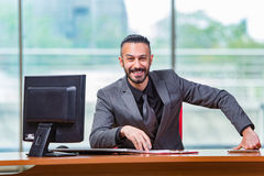 The happy businessman sitting at the desk Stock Photos