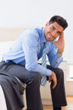 Happy businessman sitting at edge of bed looking at camera Royalty Free Stock Photos