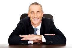 Happy businessman sitting at his desk Stock Images