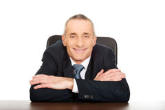 Happy businessman sitting at his desk Royalty Free Stock Photos