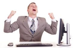 Happy businessman sitting at a laptop Stock Photo