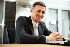 Happy businessman sitting with laptop Stock Photo