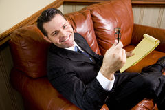 Happy businessman sitting on leather couch looking Stock Image