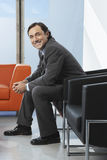 Happy Businessman Sitting In Office Lobby Royalty Free Stock Photography